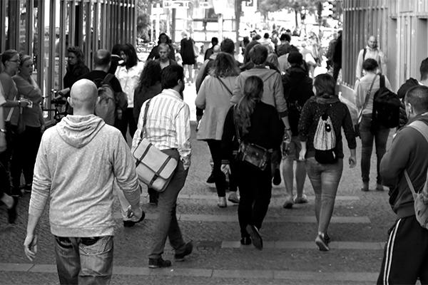 black and white photo of people walking in street